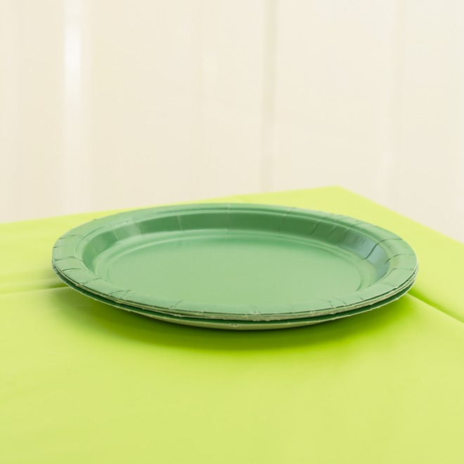 Lime green paper plates on a green tablecover.