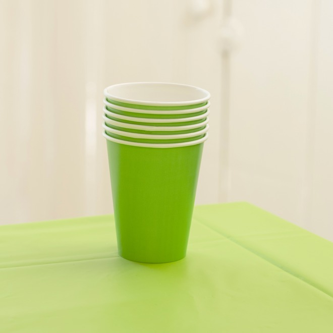 A stack of lime green paper cups sitting on a green tablecloth.