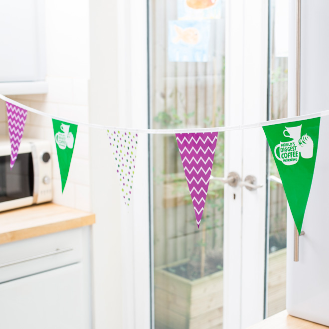 A string of purple, green and white alternating bunting, Macmillan branded.