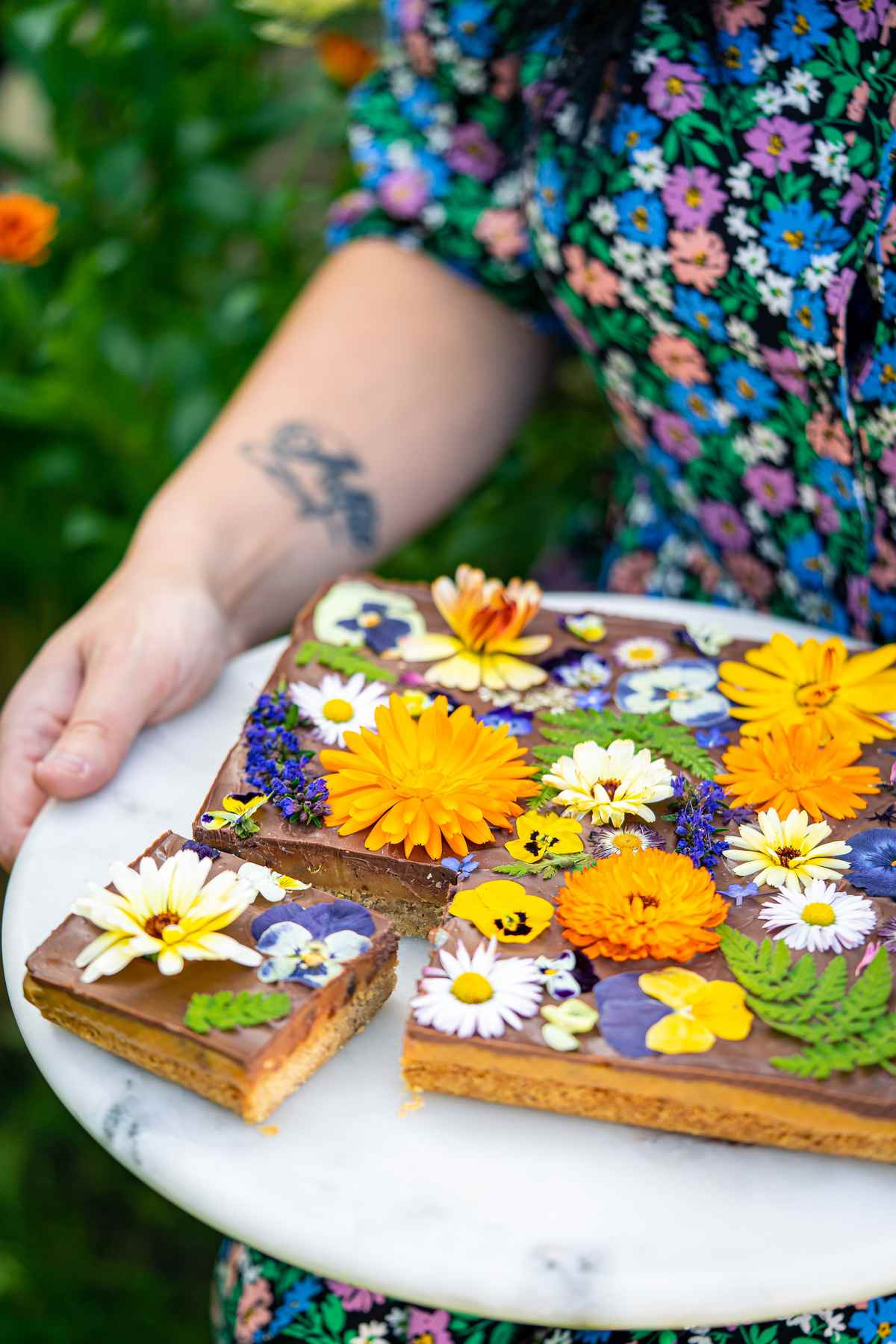 A woman holding a plate of date and pecan millionaire's shortbread. They have an assortment of flowers on the top.