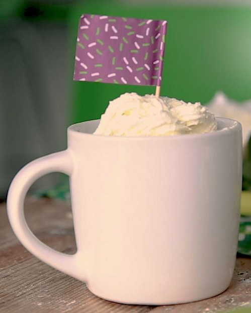 Whit mug with whipped cream on top with a mini purple Macmillan flag stuck into the top