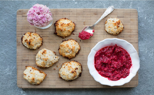 Seven macaroons on a brown board with a dish of chia seed jam
