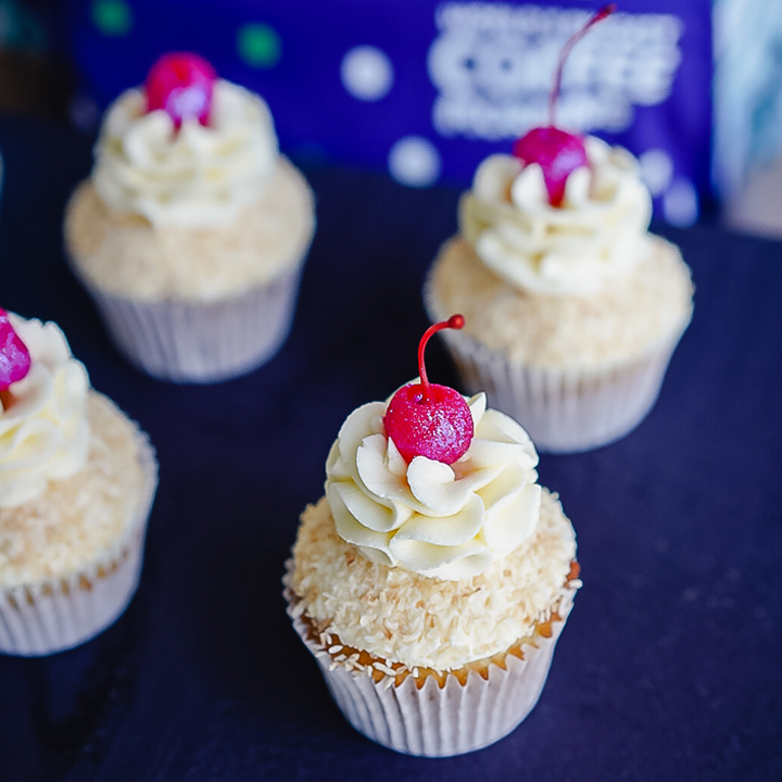 A tray of four cupcakes with frosting and cherry on top.