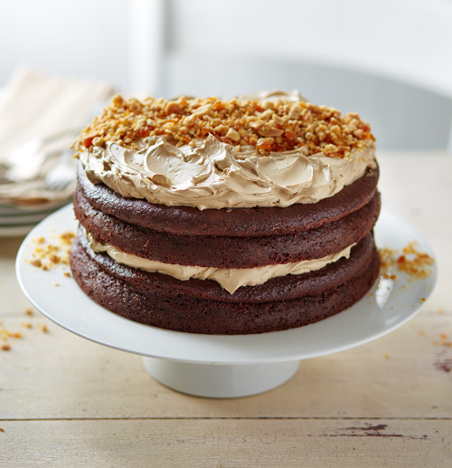 Large salted caramel cake topped with peanut brittle on a white cake stand