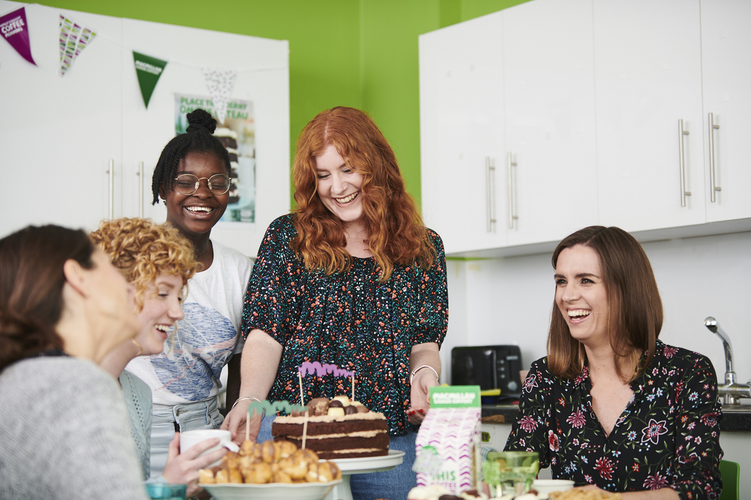 Five women around a table at a Coffee Morning smiling and talking
