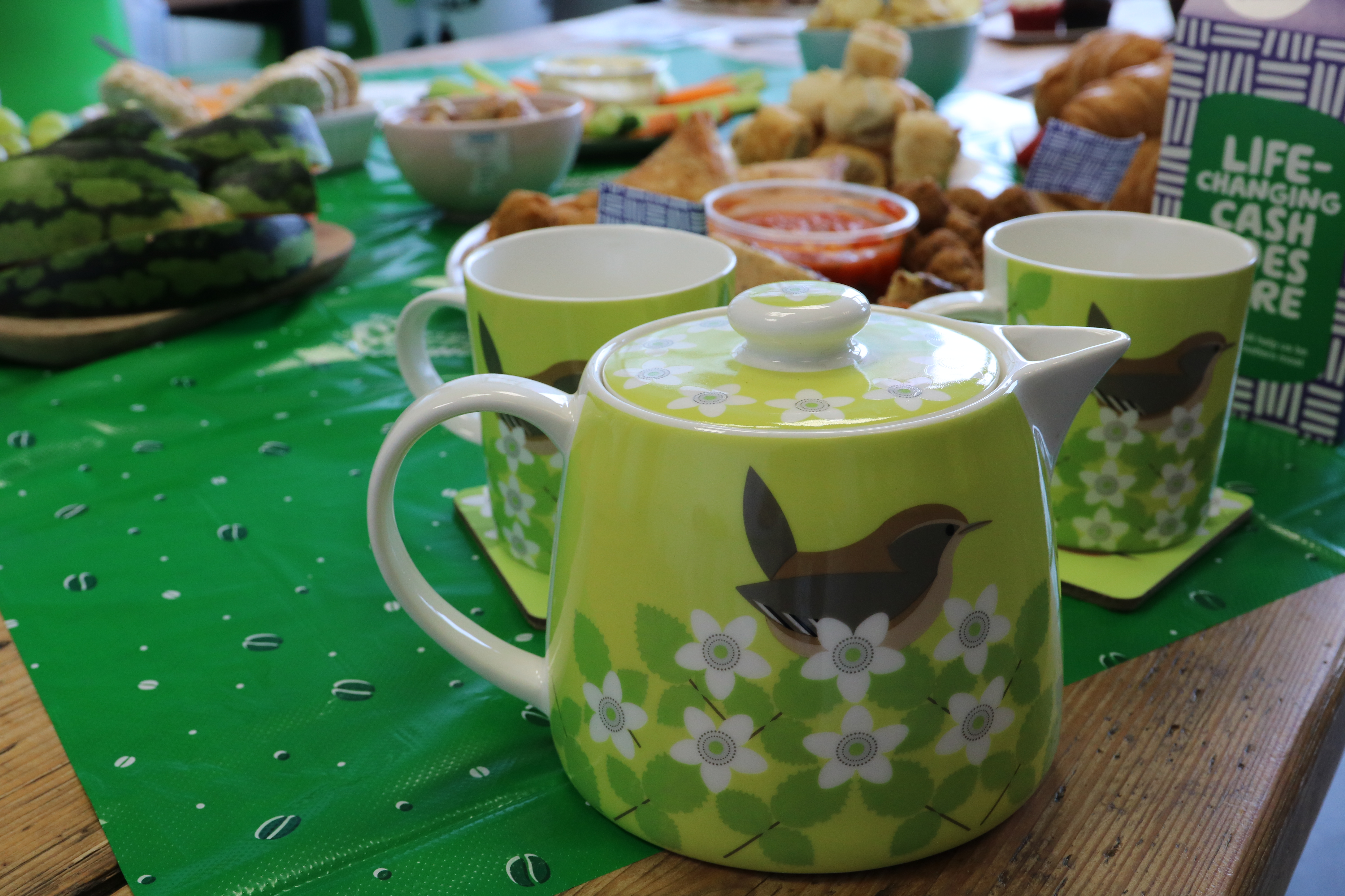 A green teapot on a table surrounded by cups and cakes.