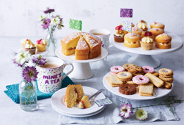Selection of cakes, biscuits and a mug of tea on white plates and cake stands