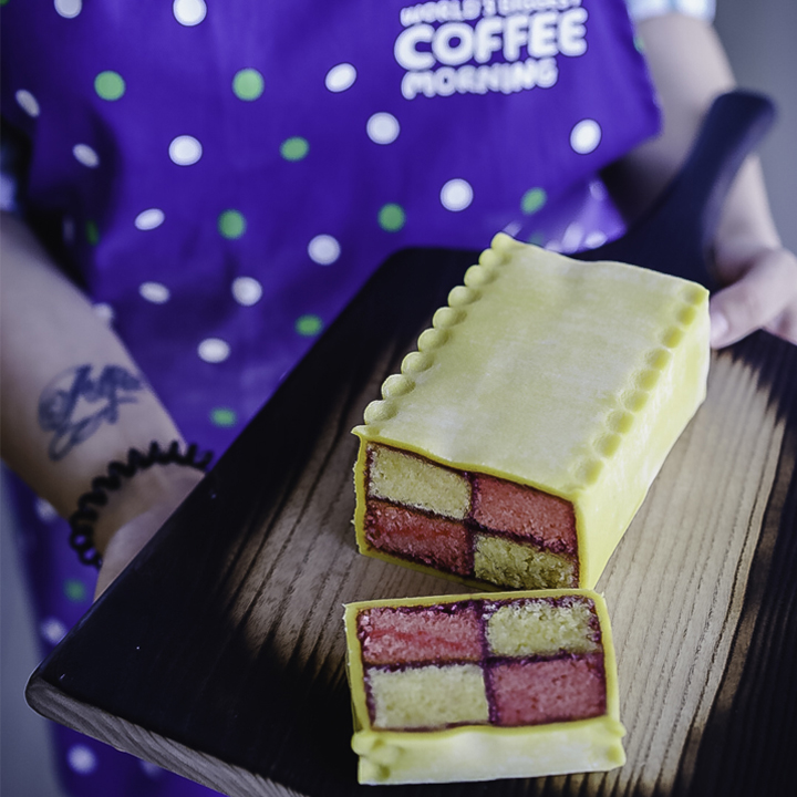 A cherry bakewell Battenberg cake on a chopping board, held by a woman with a Coffee Morning apron on.