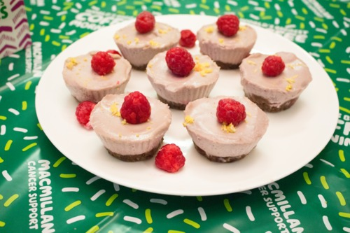 Plate of six raspberry lemon mini vegan cheesecakes on a green Macmillan tablecloth