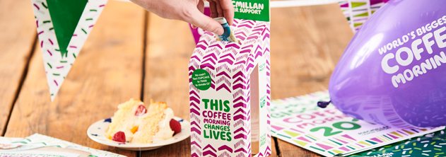 Coffee Morning table with a purple baloon and a slice of cake in the background and a hand placing a five pound note in a Macmillan donation box in the foreground