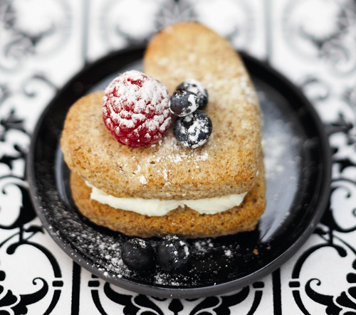 Heart shaped shortcake with single raspberry and two blueberries on top of it on small black plate
