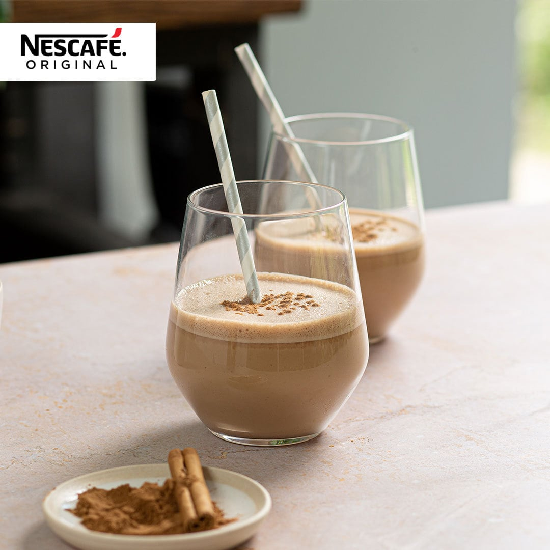 Two glasses of banana smoothie with the Nescafe logo in the corner