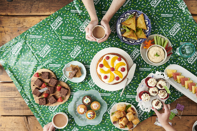 Wooden table with a spread of cakes, samosas and healthy snacks