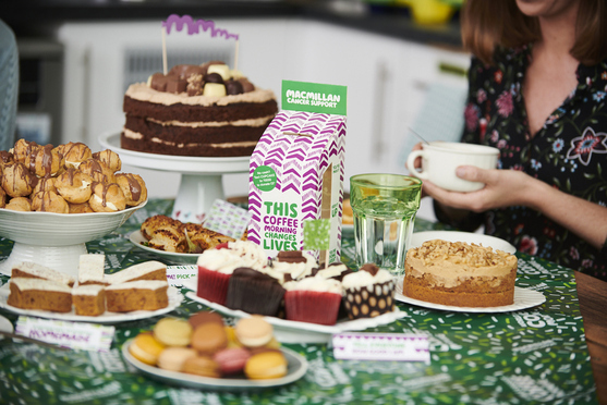 Selection of cakes on a Macmillan coffee morning table with woman holding a teacup