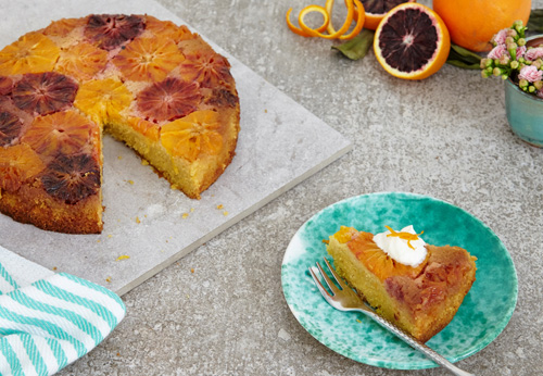 Blood orange polenta cake with one slice cut out and in a light blue bowl