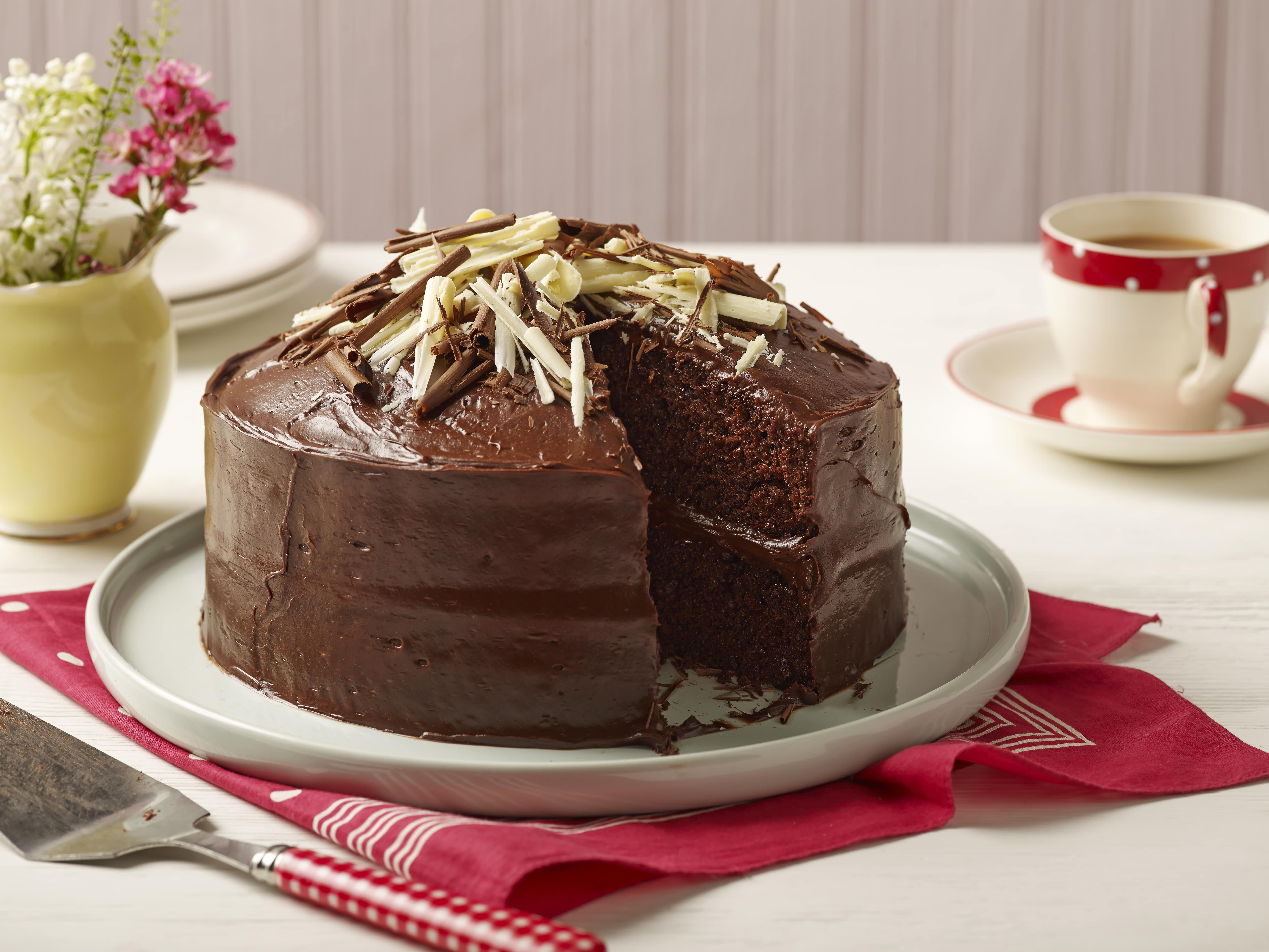 A rich chocolate cake on a plate with a slice taken out of it.