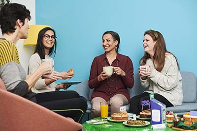 A group of women sitting in a staffroom having a chat and a cup of tea.