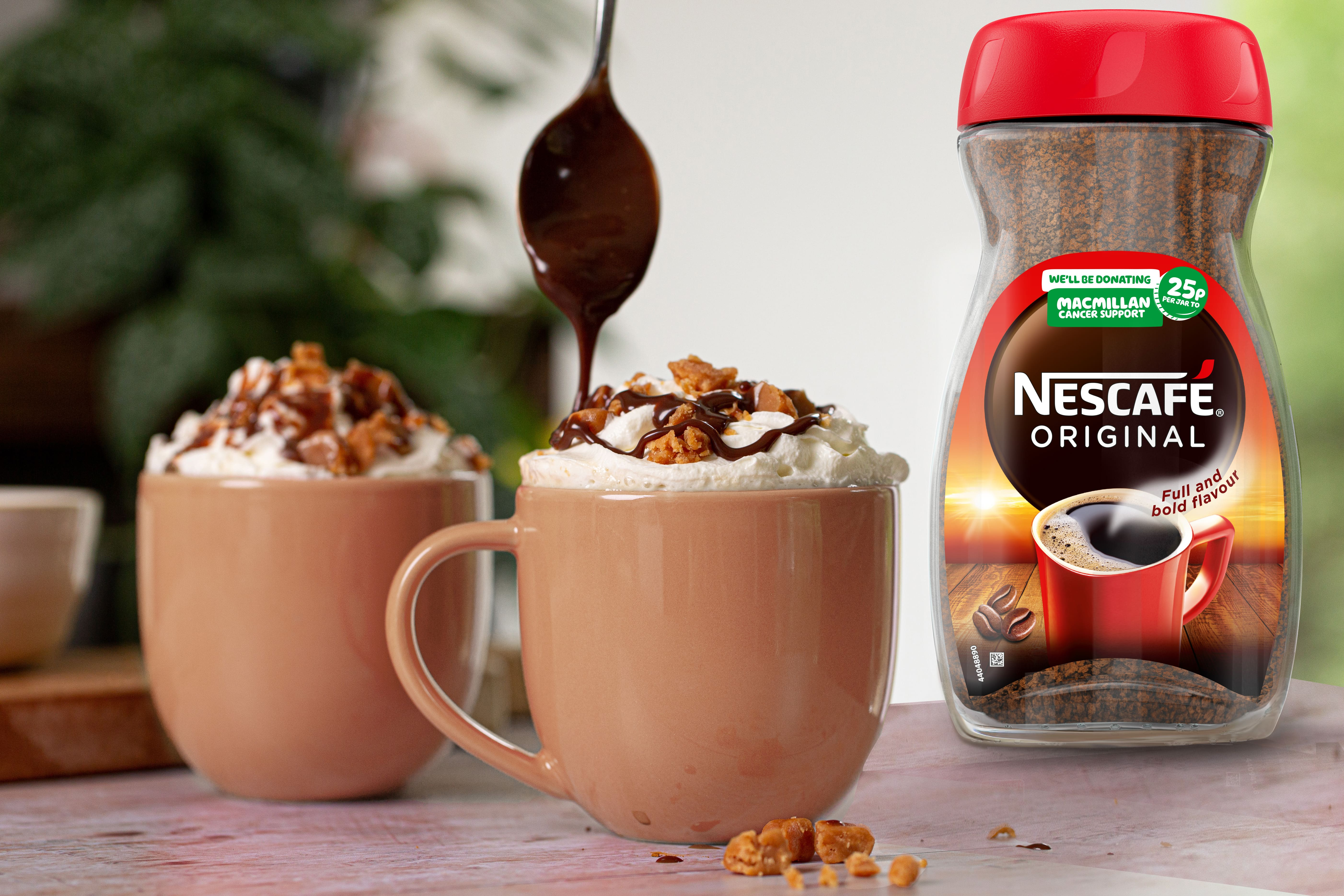 Two coffee mugs with creamy topping. One mug has a teaspoon drizzling chocolate on it. Next to the mugs is a Nescafe Original jar of coffee.
