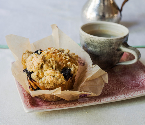 Blueberry and orange muffin on a small red plate next to a mug
