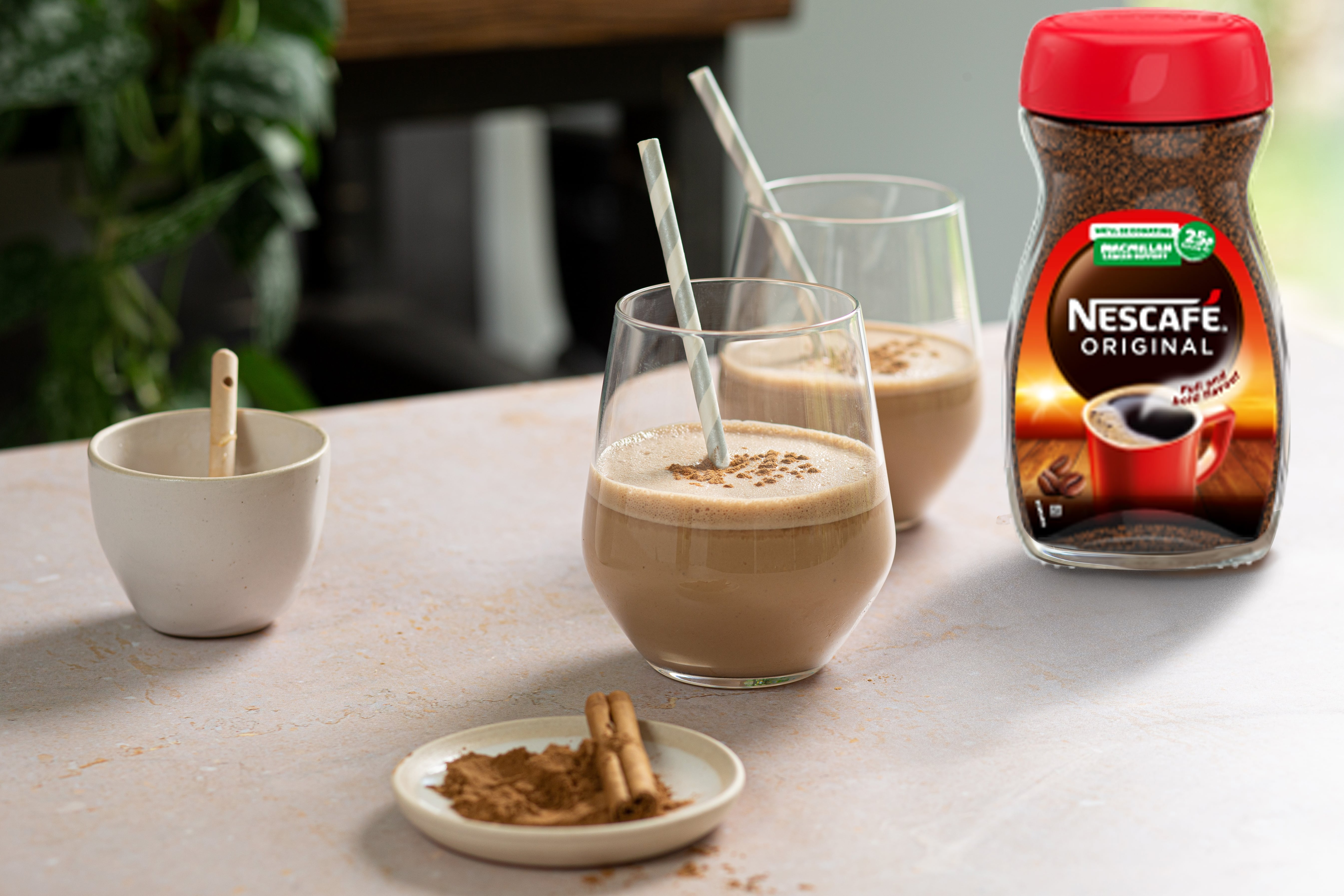 Two glasses of coffee smoothie with a straw. Nescafe original jar is next to the smoothies.