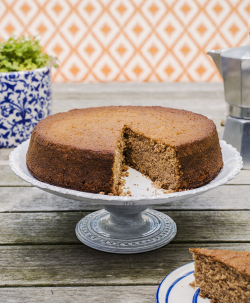 Chestnut cake with a slice cut out on a white cakes stand on top of a wooden garden bench