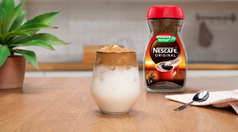 Iced coffee on a wooden surface. There is a Nescafe Original jar and spoon next to the iced coffee.