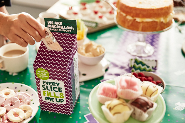 A hand placing £10 into a Macmillancollection box, on a table of baked goods.