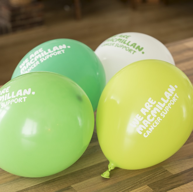 Four Macmillan balloons, one yellow, one white, one dark green and one light green
