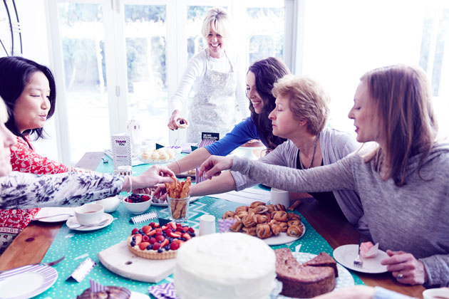 5 women sitting around a table covered in baked goods, having a great time.
