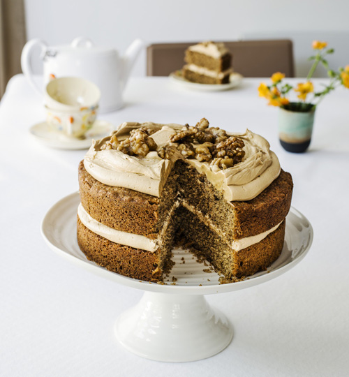 Coffe and walnut cake with a slice cut out on a white cake stand on top of a table with white tablecloth