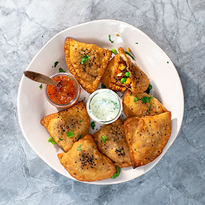 Triangular samosas on a plate with dips