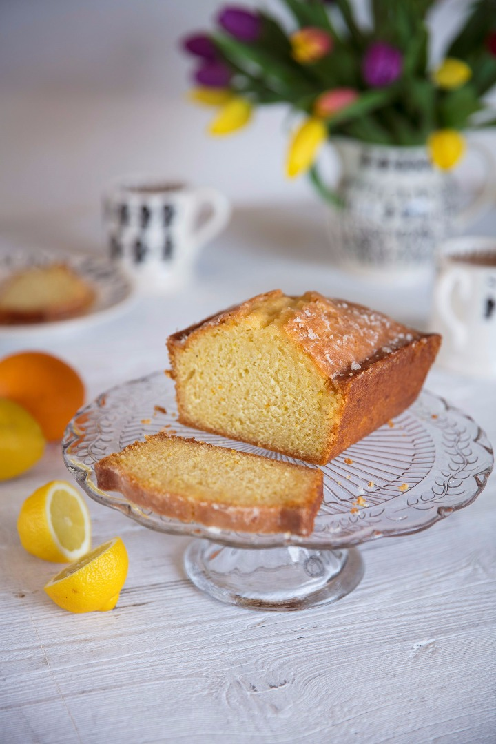 Citrus cake with a slice cut off on a cake stand