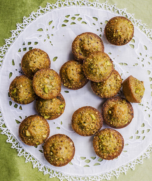 15 friands on top of a patterned doily on a green tablecloth
