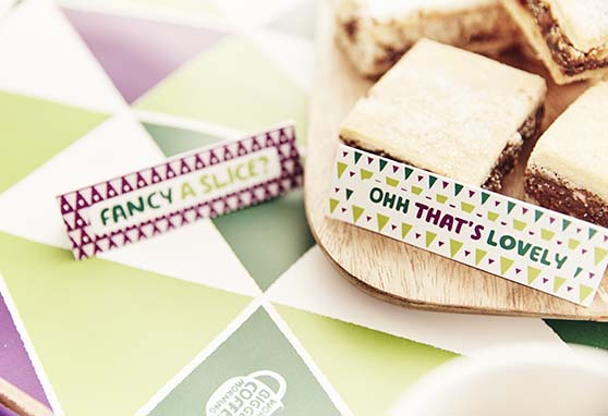 Cardboard labels that say 'fancy a slice' and 'ohh that's lovely' on a plate of cakes