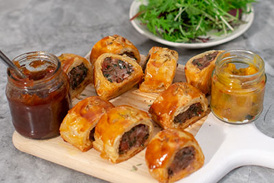 Sausage rolls on a platter with condiments