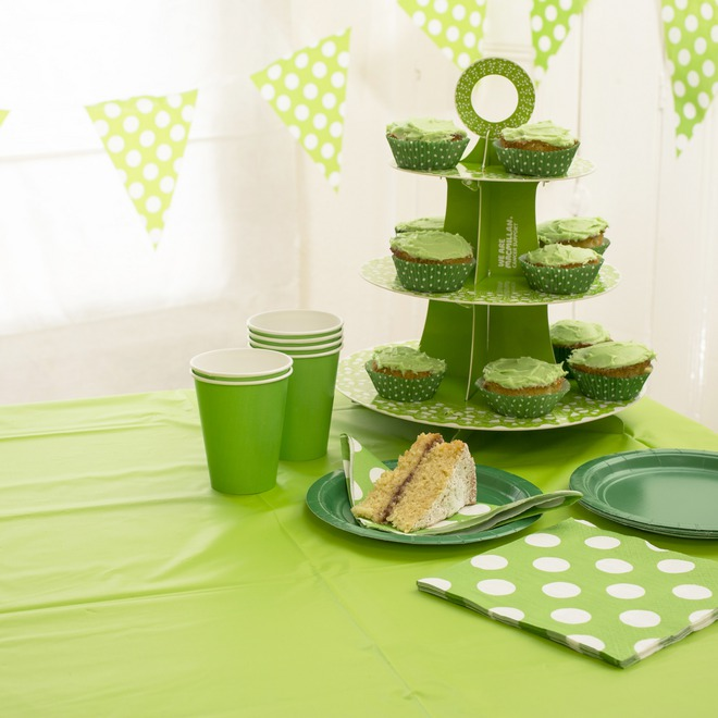 Lime green tablecover. A cake stand, plates, napkins and paper cups sit on top.