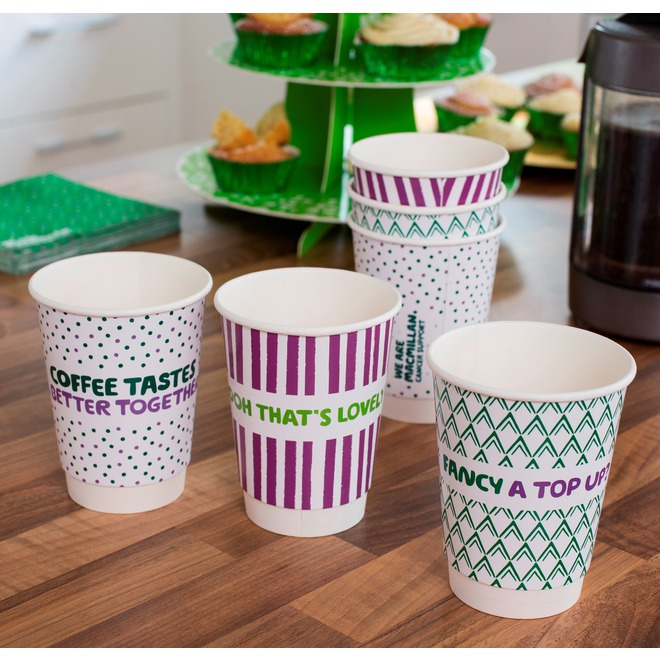 A selection of Macmillan branded paper drinking cups, on a table with a cake stand int he background.